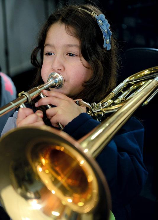 Jovem aluna do Núcleo de Música da Fundação Lia Maria Aguiar praticando instrumento de sopro