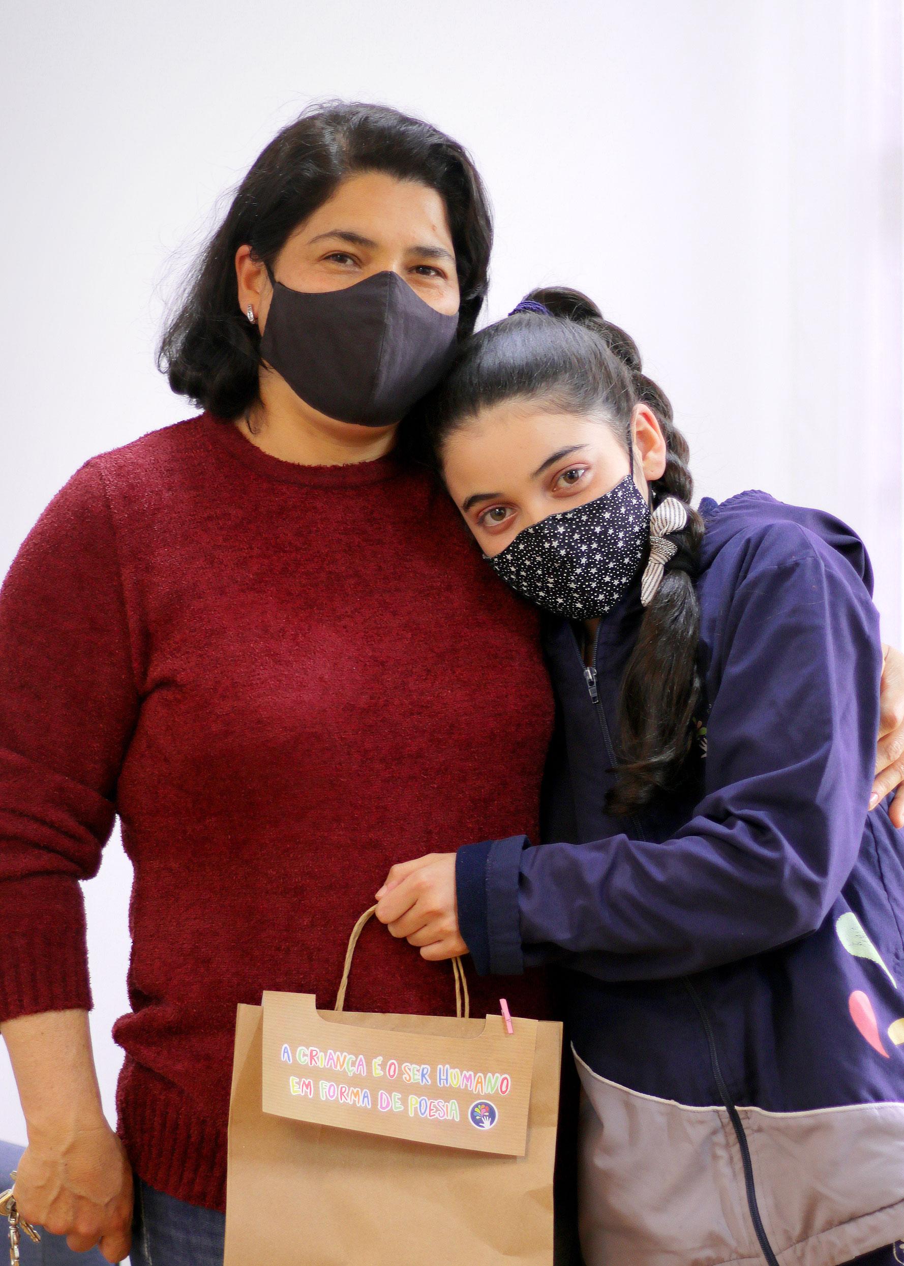Uma menina com a cabeça apoiada lateralmente no peito de sua mãe. Ela abraça a filha com um braço. A menina segura uma sacola e ambas usam máscara.