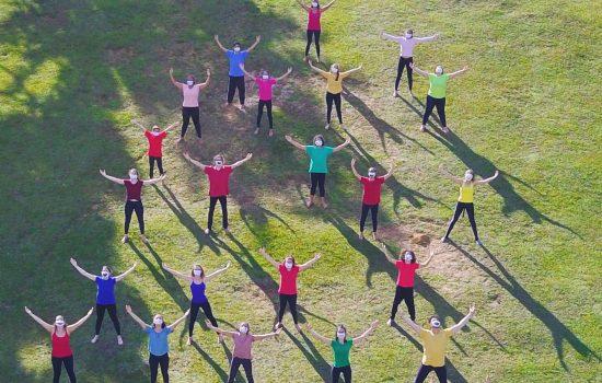 Vários jovens em uma grama com os braços abertos olhando para cima.