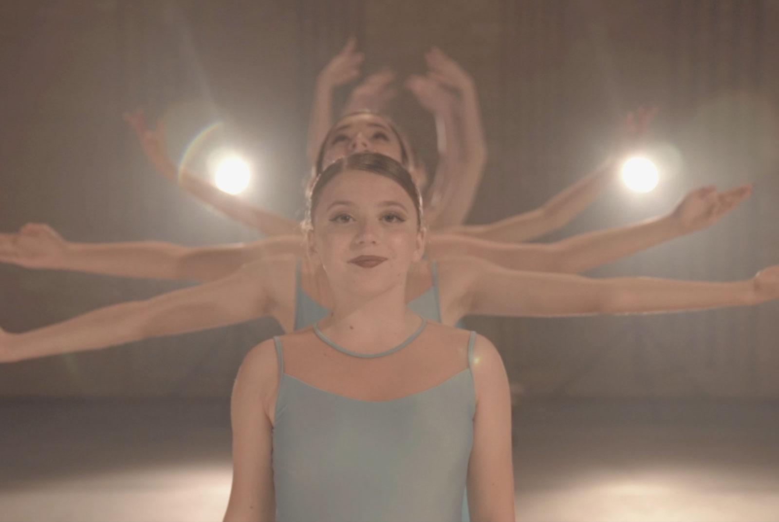 Bailarinas vestindo um figurino verde claro e ao fundo dois pequenos holofotes.