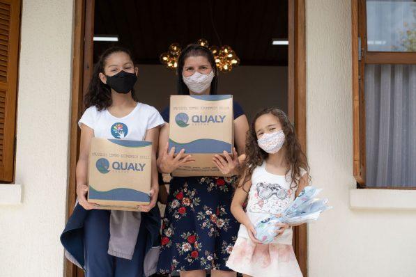 Uma mãe e duas filhas posam de frente para a foto, todas usam máscara, duas seguram uma caixa de papelão e a menor segura um ovo de Páscoa.