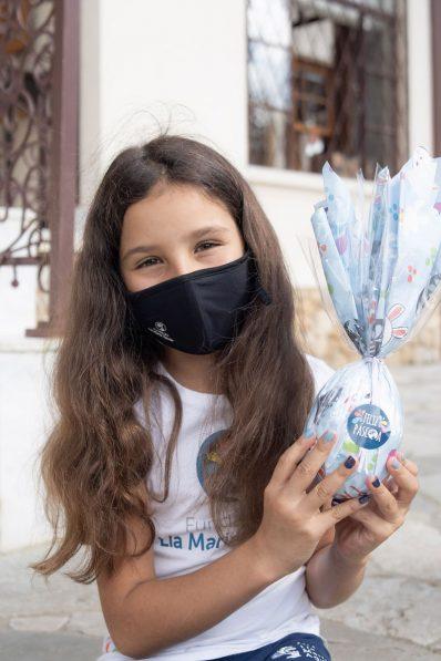 Uma menina usando o uniforme da Fundação Lia Maria Aguiar e máscara preta está sentada segurando um ovo de Páscoa azul claro.