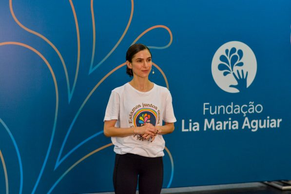 Na imagem se vê uma professora da Fundação em pé em frente a um painel azul, onde se vê a marca da instituição ao lado direito e desenhos de gotas do lado esquerdo.