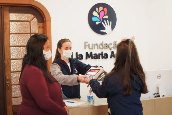 Na imagem, mãe está ao lado da filha recebem um tablet das mãos da recepcionista da FLMA. Ao fundo o logo da instituição na parede escrito Fundação Lia Maria Aguiar.